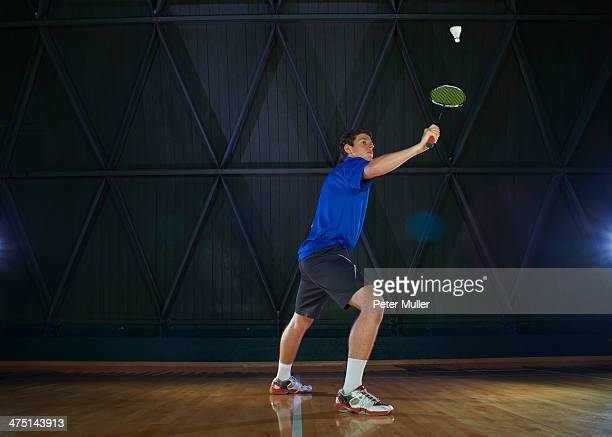 Young man playing badminton on court