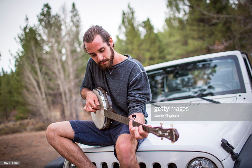 Young man playing banjo on jeep hood, Lake Tahoe, Nevada, USA