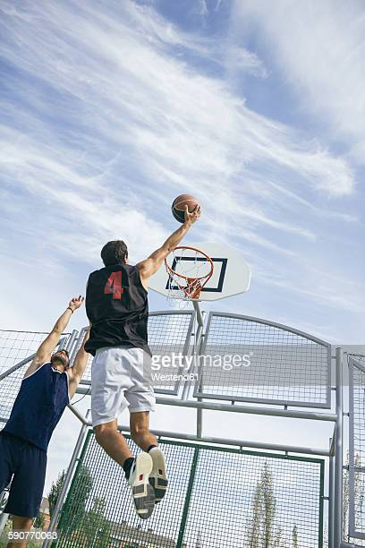 Young man playing basketball, dunking ball