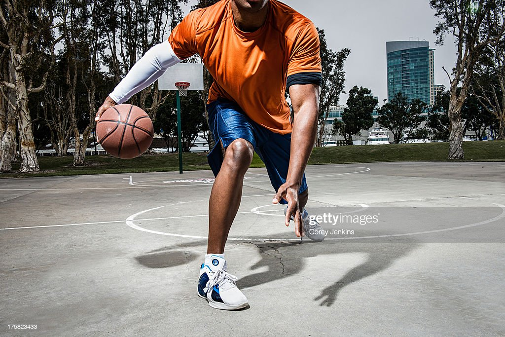 Young man playing basketball on court, close up