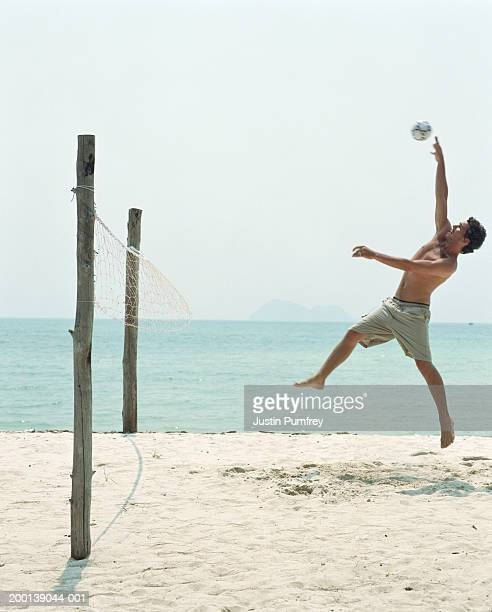 Young man playing beach volleyball, leaping for ball