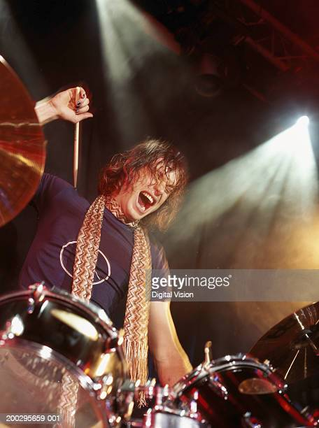 Young man playing drums, mouth open