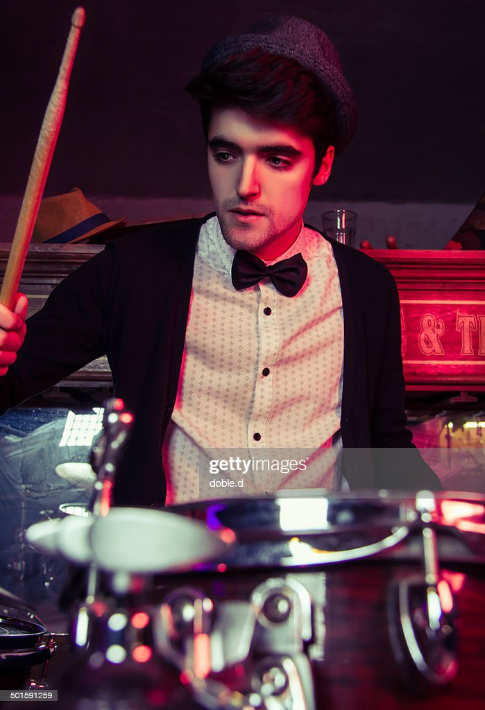 Young man playing drums on a club concert
