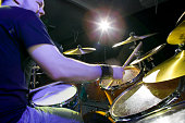 Young man playing drums on stage, portrait, low angle view