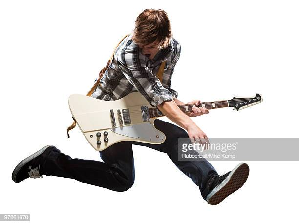 Young man playing electric guitar and jumping