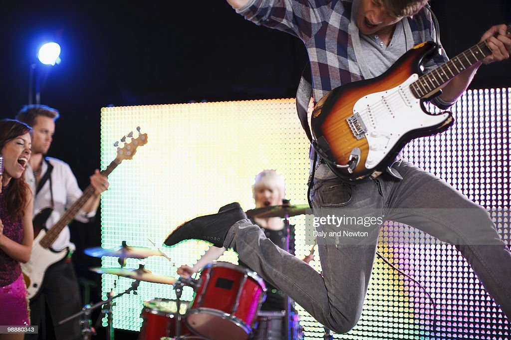 Young man playing electric guitar jumping in air : Stock Photo