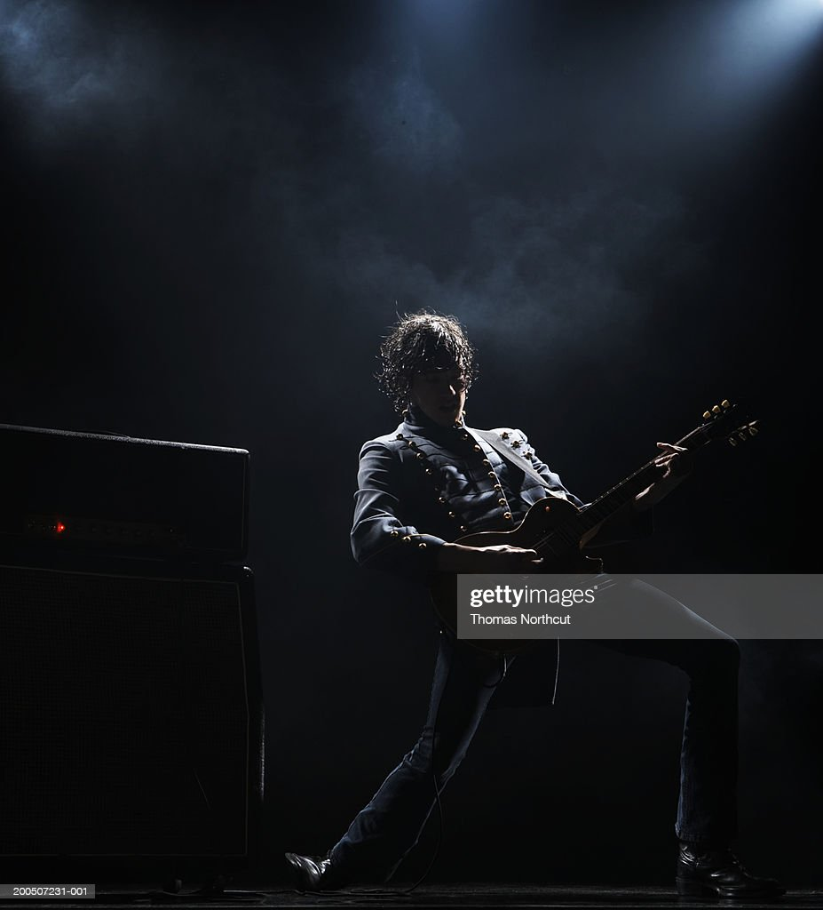 Young man playing electric guitar on dark stage : Stock Photo