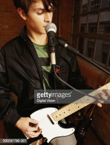 Young man playing electric guitar, singing into microphone