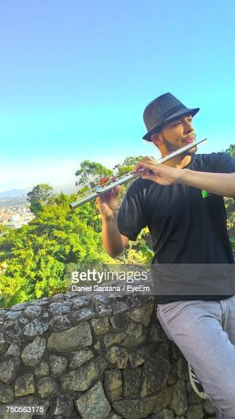 Young Man Playing Flute While Standing By Retaining Wall Against Clear Blue Sky