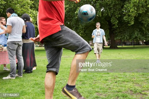 Young man playing football in park : Stock Photo