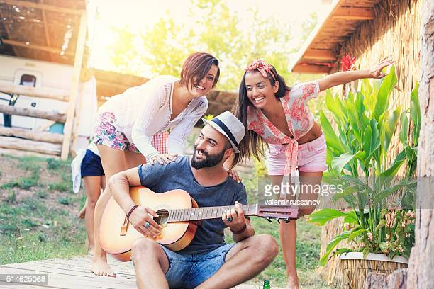 Young man playing guitar in front of a caravan