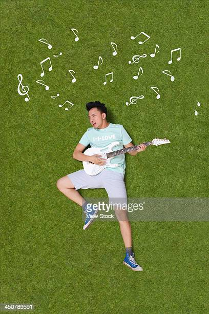 Young man playing guitar on grass