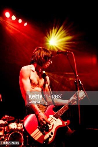Jovem Tocar Guitarra no palco no concerto : Foto de stock