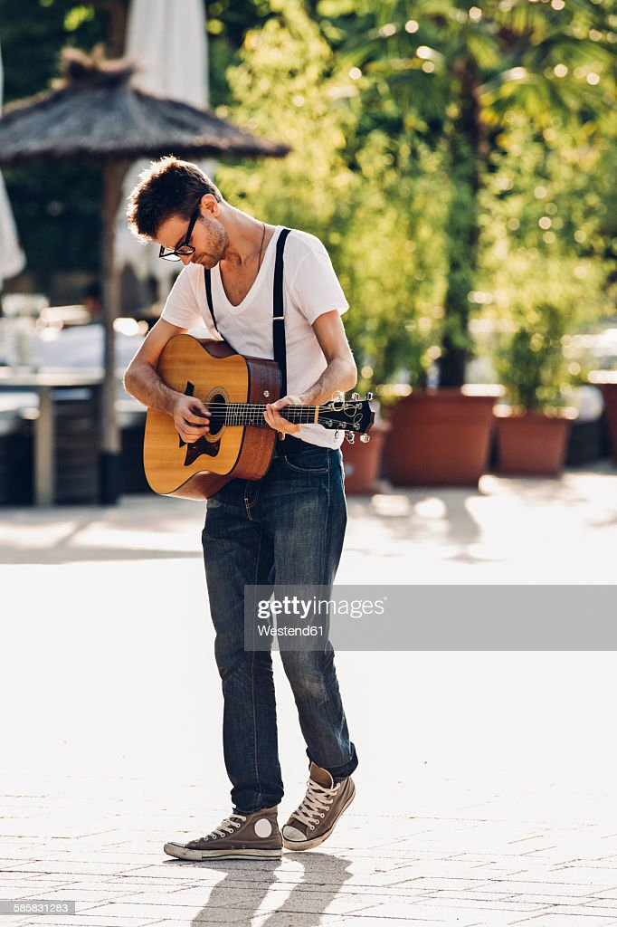 Young man playing guitar on the street