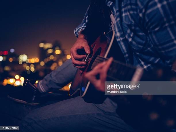 Junger Mann spielt Gitarre sitzen auf dem Dach bei Nacht
