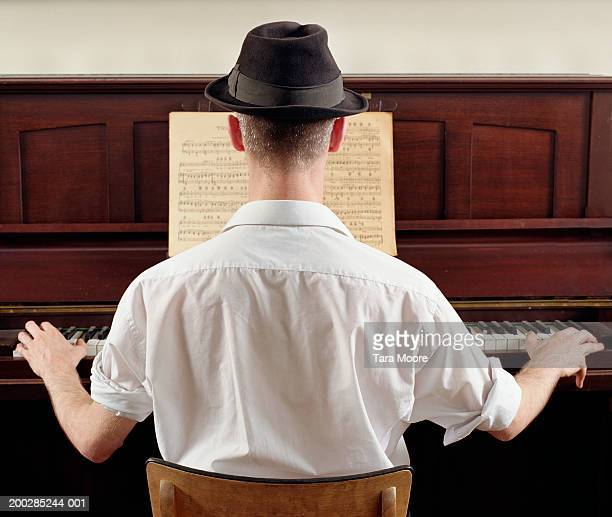 Young man playing piano, rear view, close-up