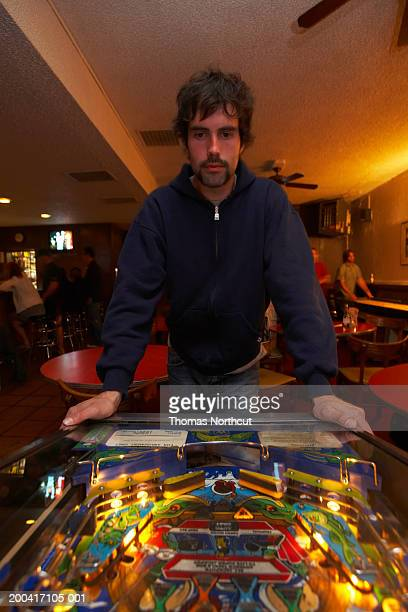 Young man playing pinball in bar