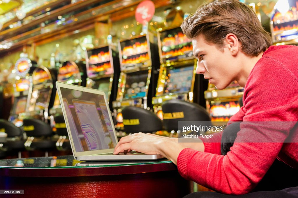 Young man playing poker on his laptop