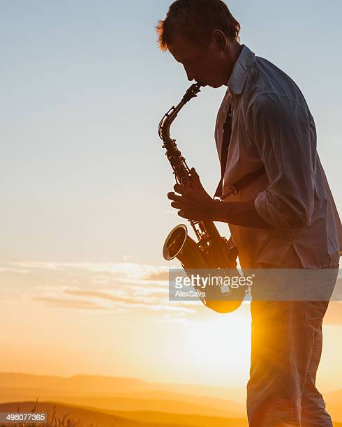 young man playing saxophone outdoor at sunset