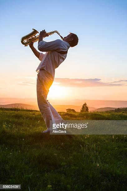 Giovane uomo giocare Sassofono aperto al tramonto