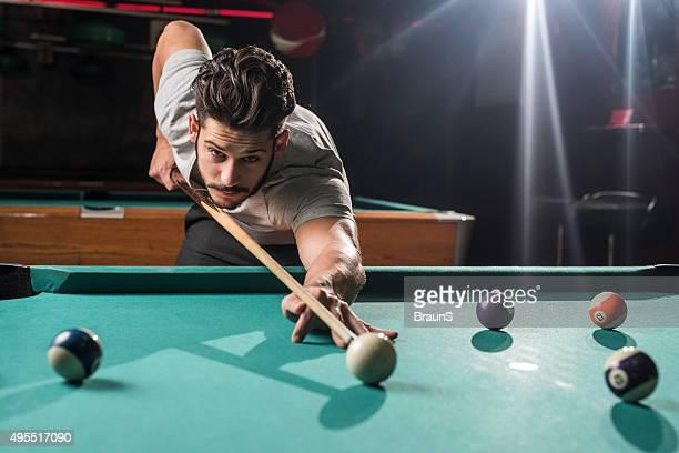 Junger Mann spielen Sie Billard in einem pub.