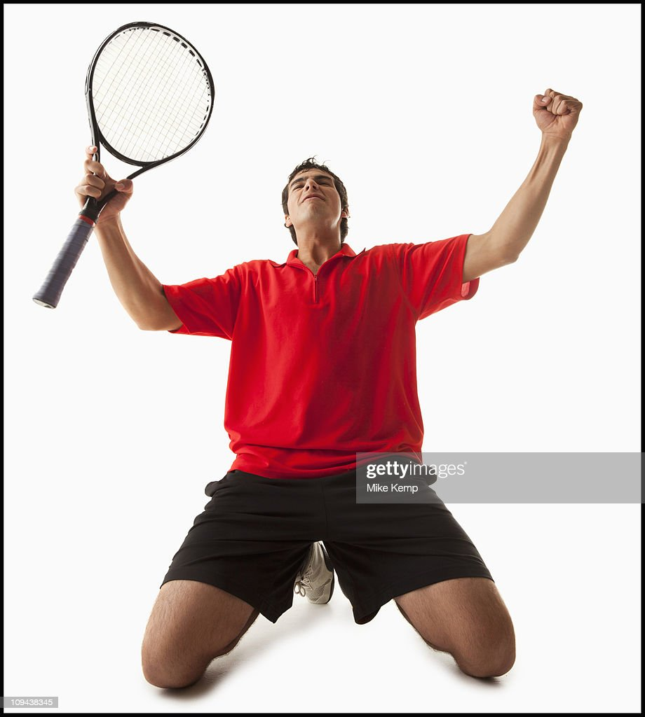 Young man playing tennis winning : Stock Photo