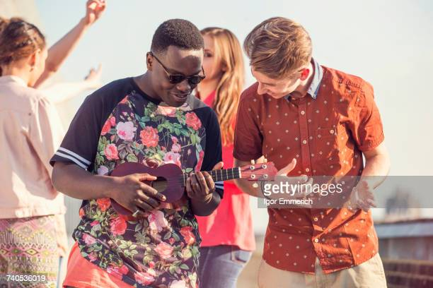 Young man playing ukulele at roof party in London, UK