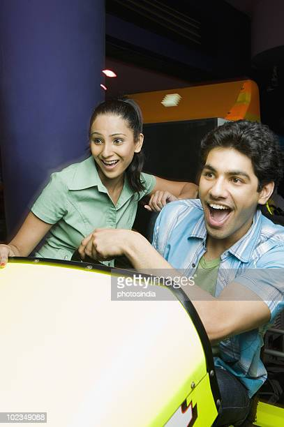 Young man playing video game and a young woman watching his game in a video arcade