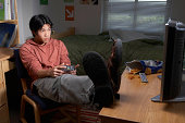 Young man playing video game in dorm room, close-up