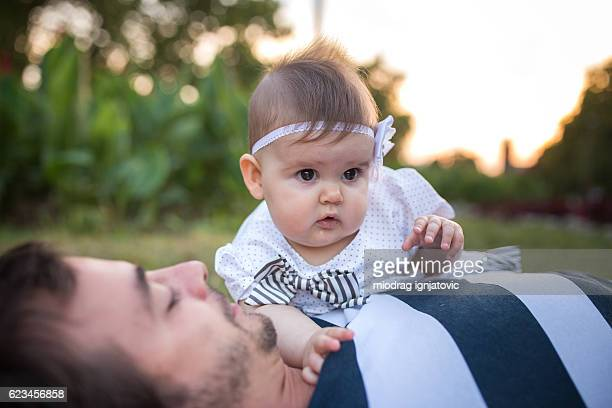Young man playing with baby
