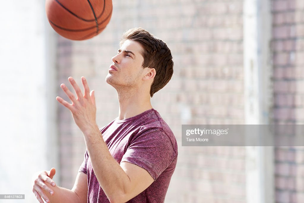 Young man playing with basketball in urban street