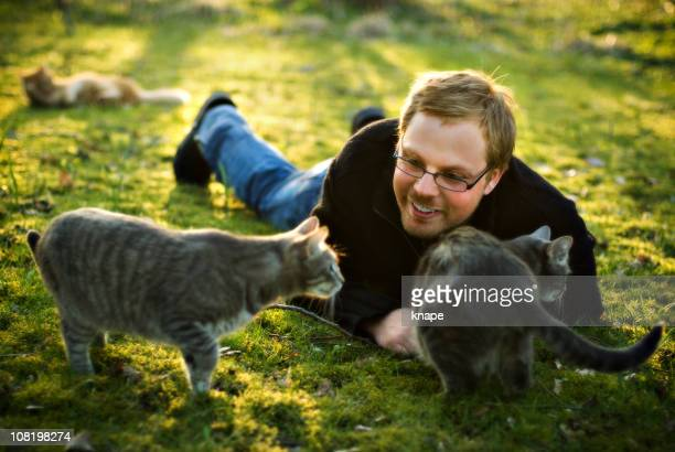 Young Man Playing With Cats