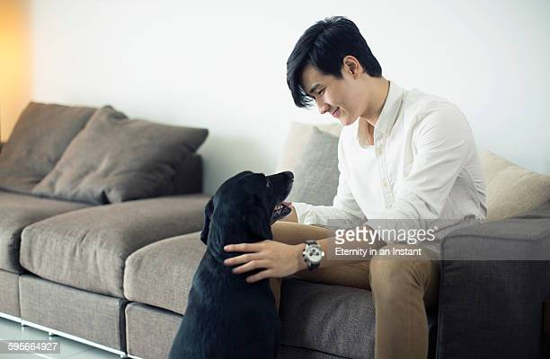 Young man playing with his dog at home.