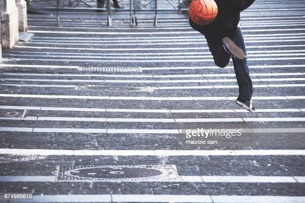 Young man playing with soccer ball on road