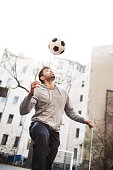 Pakaistanian man playing with a soccer ball at urban soccer place.