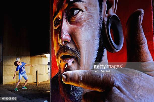A young man plays football next to a mural underneath the Caledonian Railway Bridge in Clyde Street on October 26 2016 in Glasgow Scotland The murals...