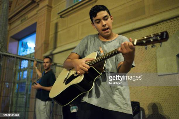 A young man plays guitar at the Pau CLaris polling station Retired people students children neighbours parents gathered in Pau Claris highschool in...