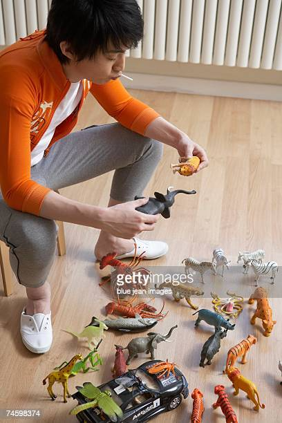 Young man plays with toys and sucks on a lollipop.