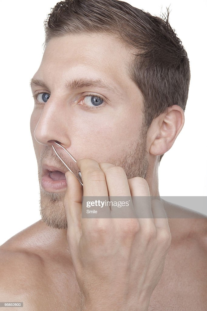 Young man plucking his nose hairs : Stock Photo