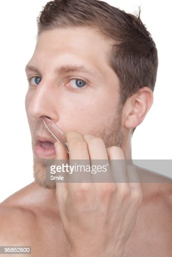 Young man plucking his nose hairs : Foto stock