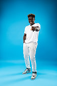 You are funny. Full length portrait of cheerful guy in white clothes isolated on blue background