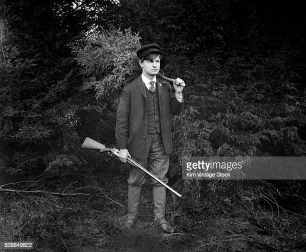 A young man poses for a portrait holding a shotgun and a small Christmas tree in New York State