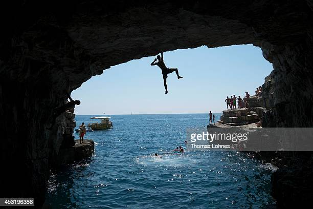 A young man poses while he climbs in an 8 to 10 meterhigh cave of Stoja on August 4 2014 near Pula Croatia Deep Water Soloing free climbing over...