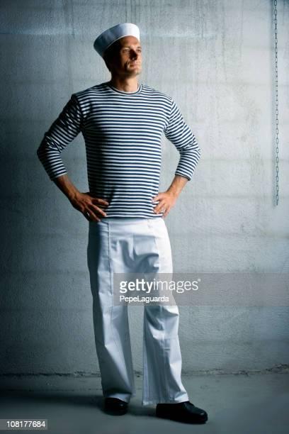 Giovane uomo in posa e vestito come un marinaio