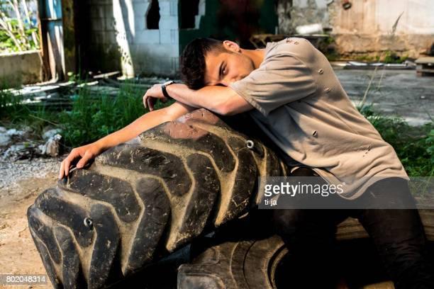 若い男がトラックのタイヤでポーズ