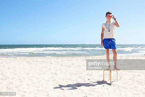 Young man posing on top of stool on beach, Port Melbourne, Melbourne, Australia