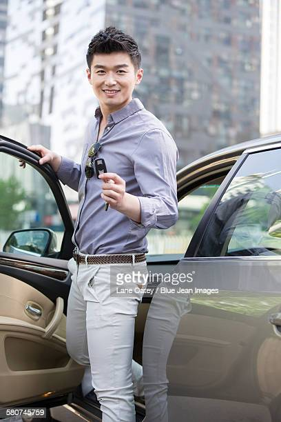 Young man posing with keys to his new car