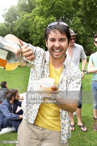 A young man pouring cider in to a plastic cup : Stock Photo