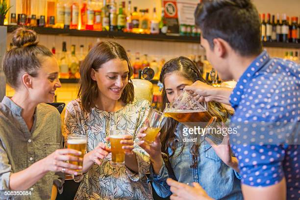 Young Man Pouring Drinks For Girls in a Bar