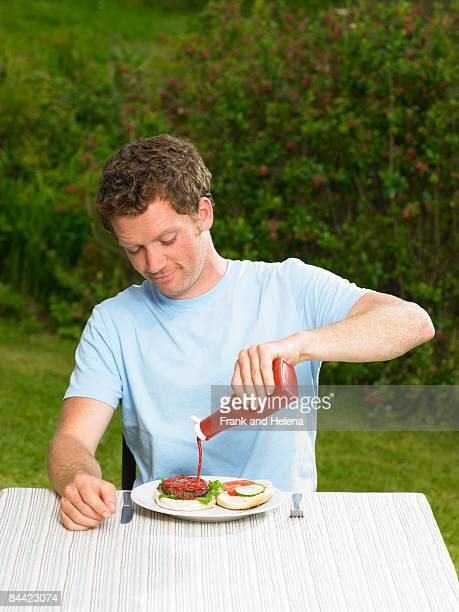 Young man pouring ketchup on burger